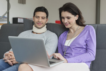 Woman using a laptop with her husband beside her
