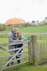 Man standing with his daughter in a farm with an umbrella