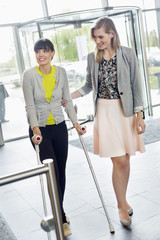 Woman helping a disabled woman in walking