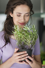 Woman smelling a rosemary plant