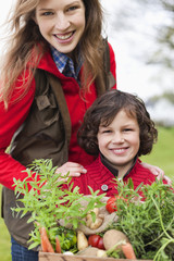 Mother and son with a crate of homegrown vegetables