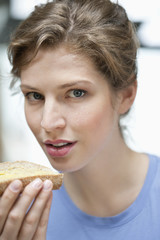 Portrait of a woman eating a bread