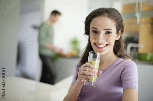 Woman drinking soup with her husband preparing food in the background