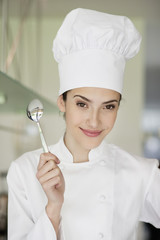 Happy female chef holding a spoon