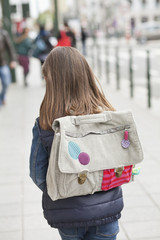 Rear view of a schoolgirl walking on footpath