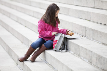 Girl taking out food from her schoolbag