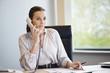 Businesswoman talking on a landline phone in an office