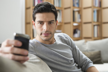 Man resting on a couch and using a mobile phone