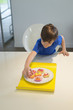 Boy picking a cup cake from plate