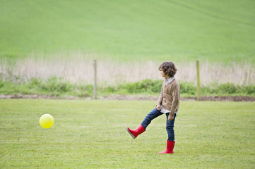 Boy playing with a ball in a field