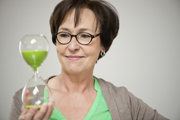 Woman looking at an hourglass and smiling