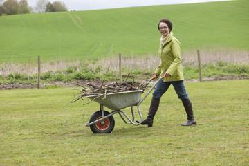 Woman pushing a wheelbarrow full of branches