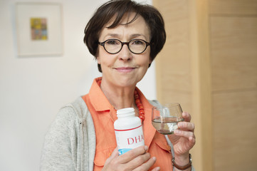 Elderly woman holding bottle of food supplement in the kitchen