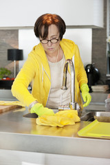 Elderly woman cleaning kitchen worktop