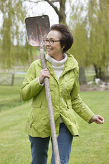 Woman walking with a spade in a park