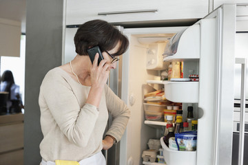 Elderly woman looking at a refrigerator and talking on a mobile phone