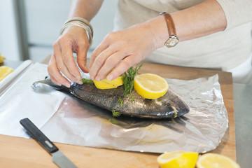 Elderly woman preparing seafood in a kitchen