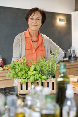 Woman standing in the kitchen with an organic plant