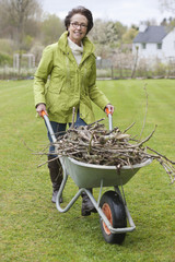 Woman pushing a wheelbarrow full of branches