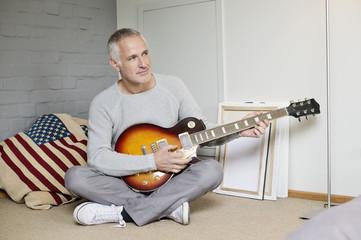 Man playing a guitar at home