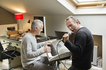 Two male friends playing a piano and singing