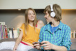 Teenage boy listening to music on iPod with his sister at home