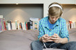 Teenage boy listening to music on iPod at home