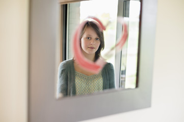 Girl looking at reflection in mirror decorated with heart shape