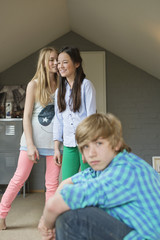 Portrait of a teenage boy with his two sisters whispering in background