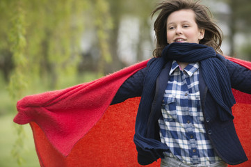 Girl holding a blanket with her arm outstretched