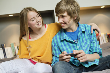 Teenage boy with his sister using a mobile phone and smiling