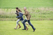 Happy family running in a field