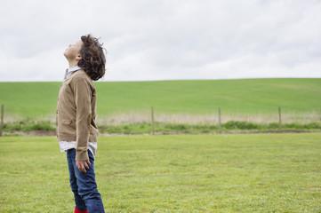 Boy daydreaming in a field