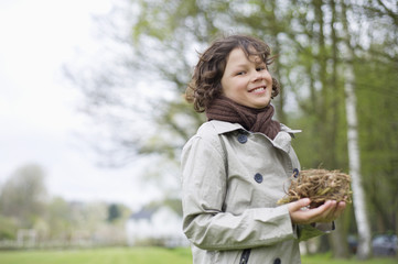 Portrait of a boy holding a bird's nest in a park