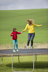 Woman with her son jumping on a trampoline in a field