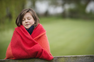 Girl wrapped in a blanket with her eyes closed in a farm