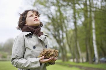 Close-up of a boy holding a bird's nest in a park