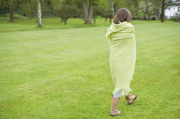 Girl wrapped in a blanket and walking in a field