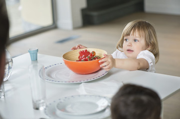 Little girl placing fruit bowl on dining table