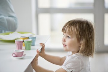 Cute girl with toy tea set near a dining table