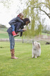 Woman carrying her daughter on piggyback and scolding her dog