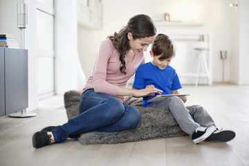 Woman looking at her son using a digital tablet