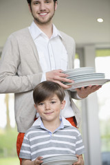 Man and son arranging plates for lunch