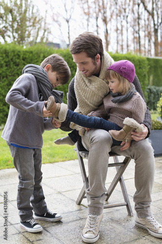 Boy putting shoe on his sister sitting in her father's lap