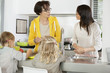 Two girls with her mother and grandmother discussing in a kitchen