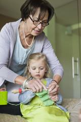 Little girl learning knitting from her grandmother