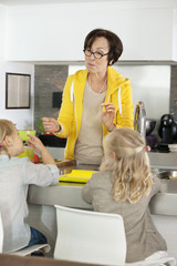 Elderly woman with her granddaughters in a kitchen