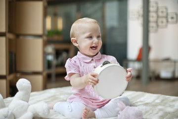 Baby girl playing with a tambourine