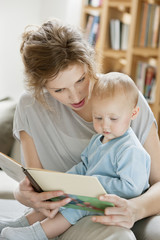 Woman teaching her daughter from a picture book