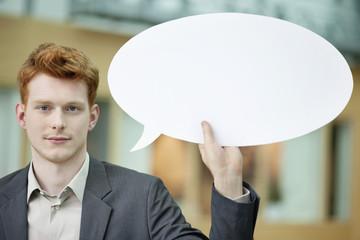 Businessman holding a speech bubble in an office